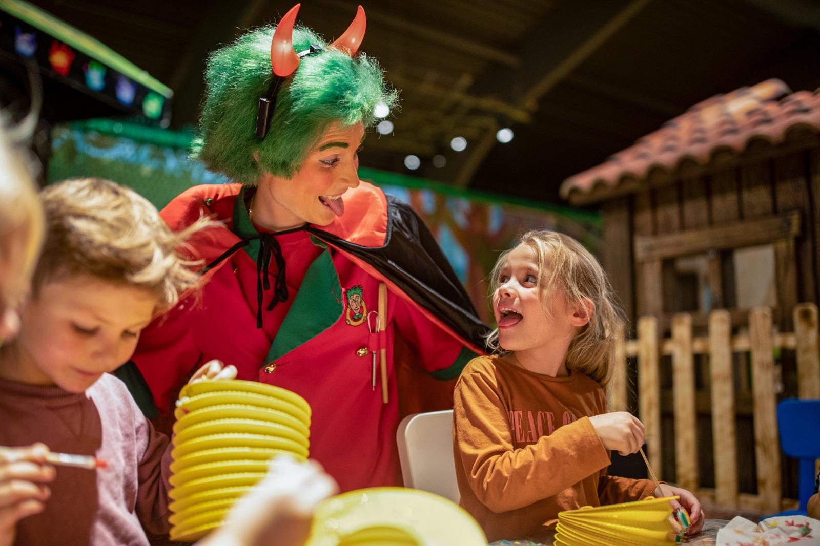 Femme déguisée en diable avec petite fille tirant la langue