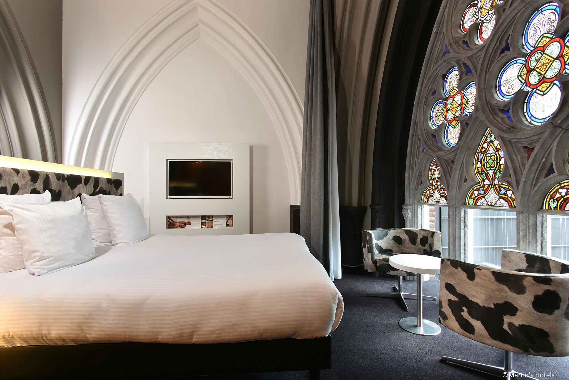 chambre double avec vitraux colorés dans le Martin's Dream Hotel à Mons.