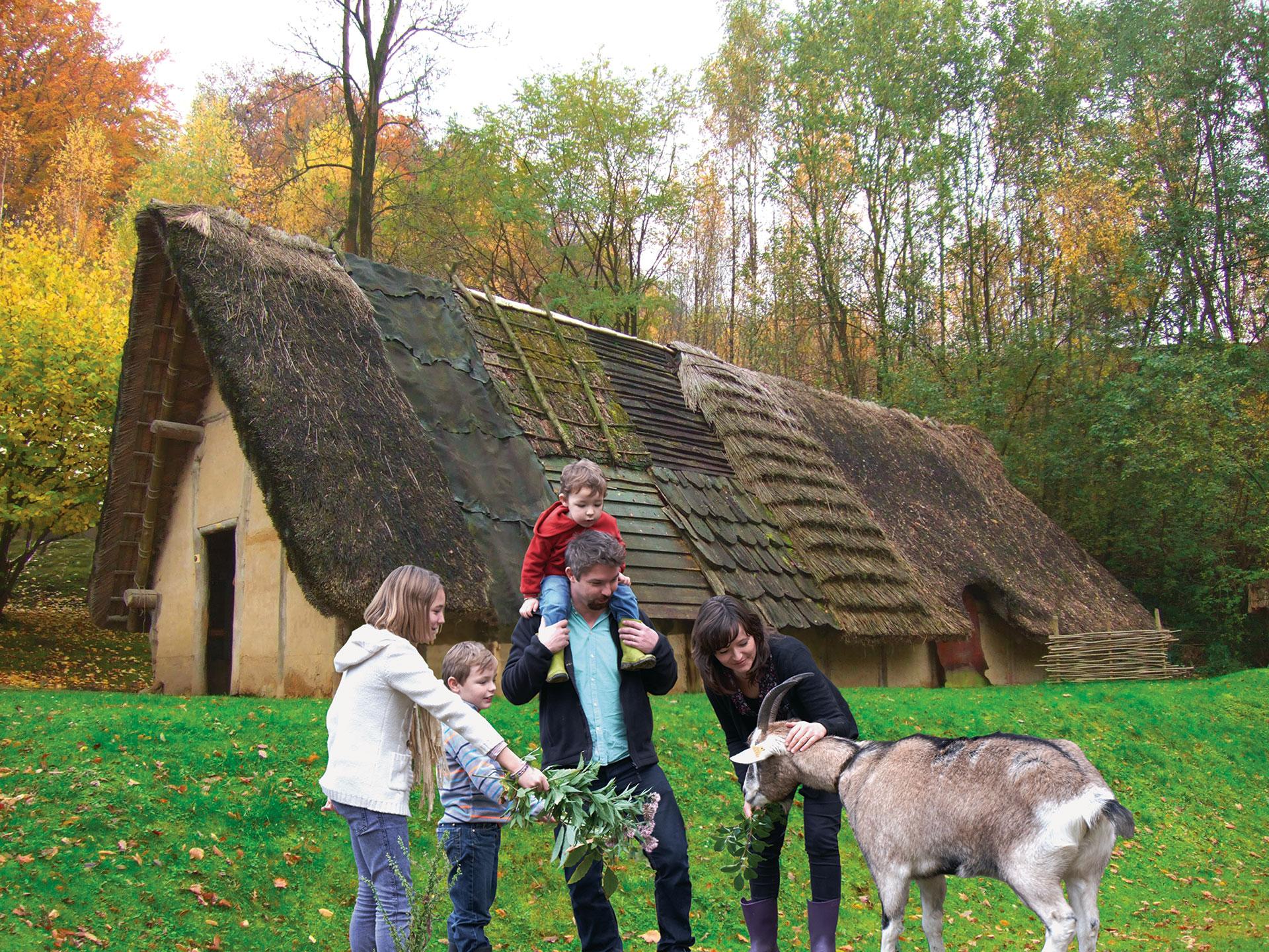 famille dehors, devant une hutte, au Préhistomuseum