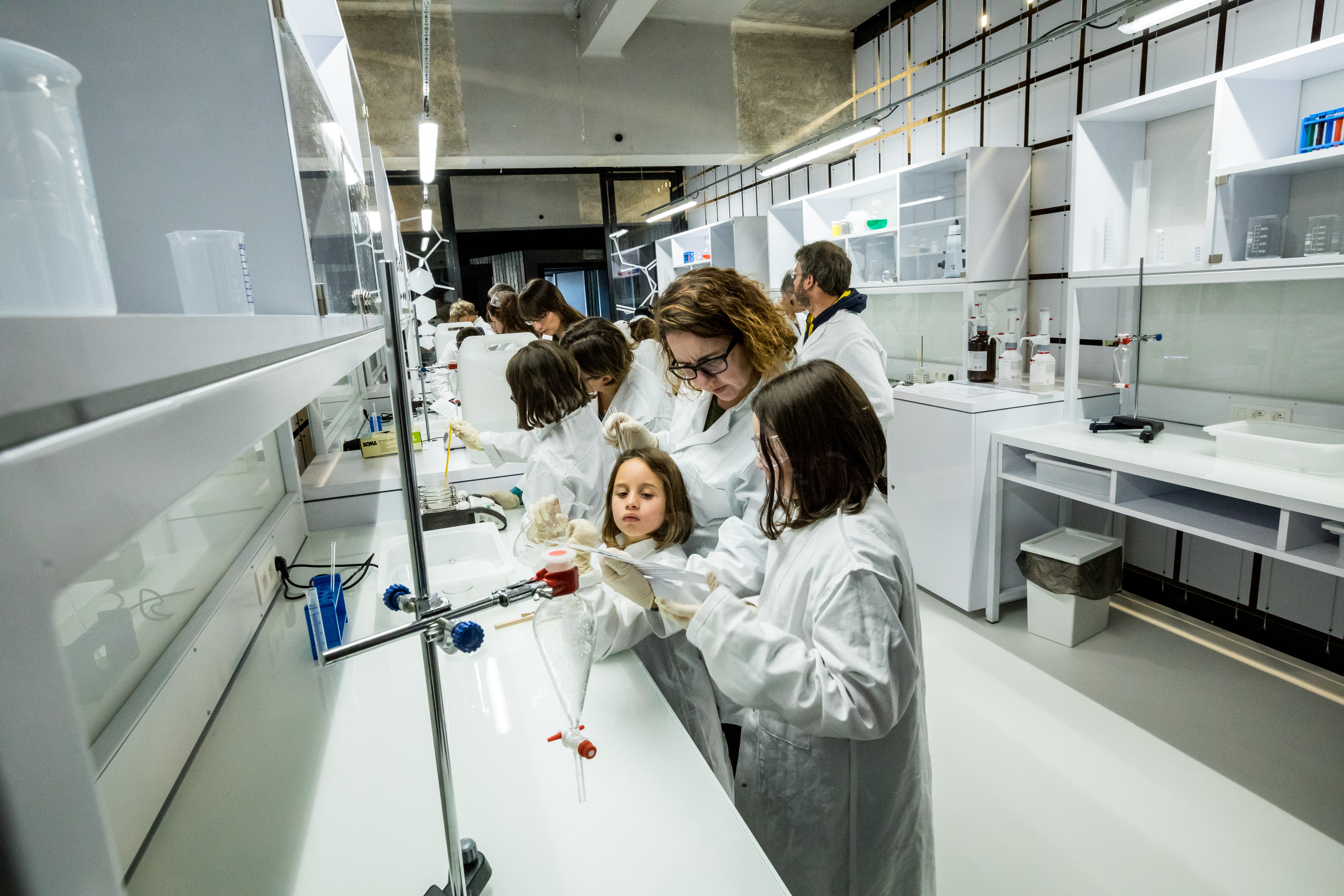 Des enfants, accompagnés d'adultes, réalisent des expériences dans le labo du Pass à Frameries