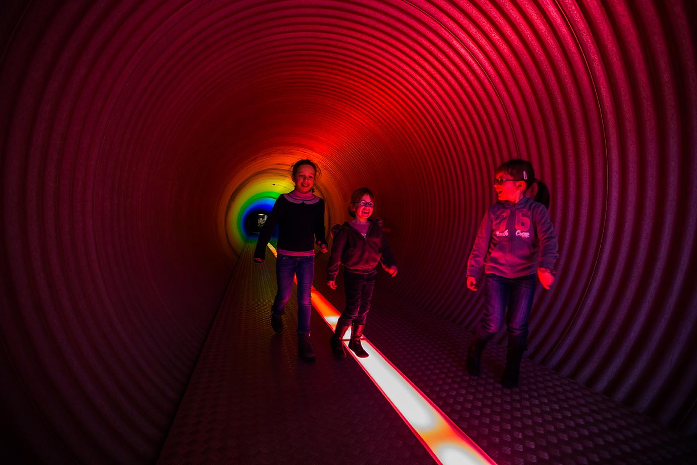 Un groupe de filles traverse un tunnel du parcours de visite de Pass à Frameries
