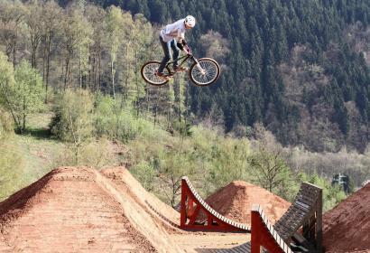 Un biker effectue un saut en VTT dans le parcours du bike part de la Ferme Libert