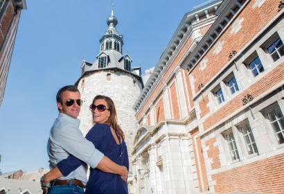 Un couple souriant pose en face du Beffroi de Namur