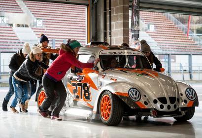équipe poussant une voiture de course sur le circuit de Spa-Francorchamps
