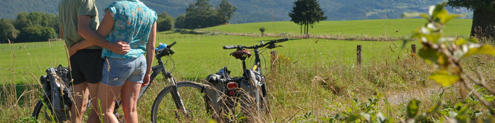 Un couple regardant à l'horizon, un vélo à côté d'eux
