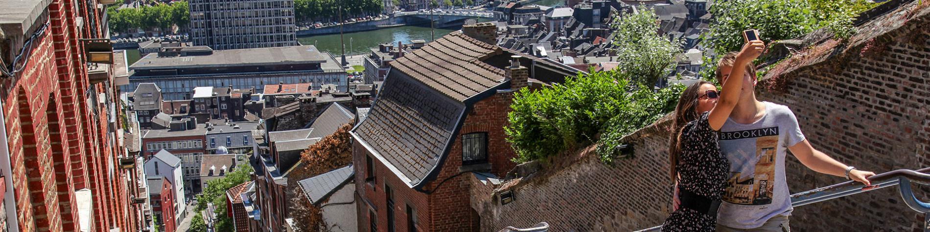 Un couple au somme de l'escalier de la montagne de Bueren, un lieu emblématique de la ville de Liège.