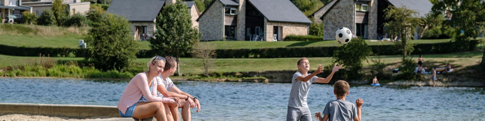 Famille se baignant dans le lac avec en arrière plan le village de vacances