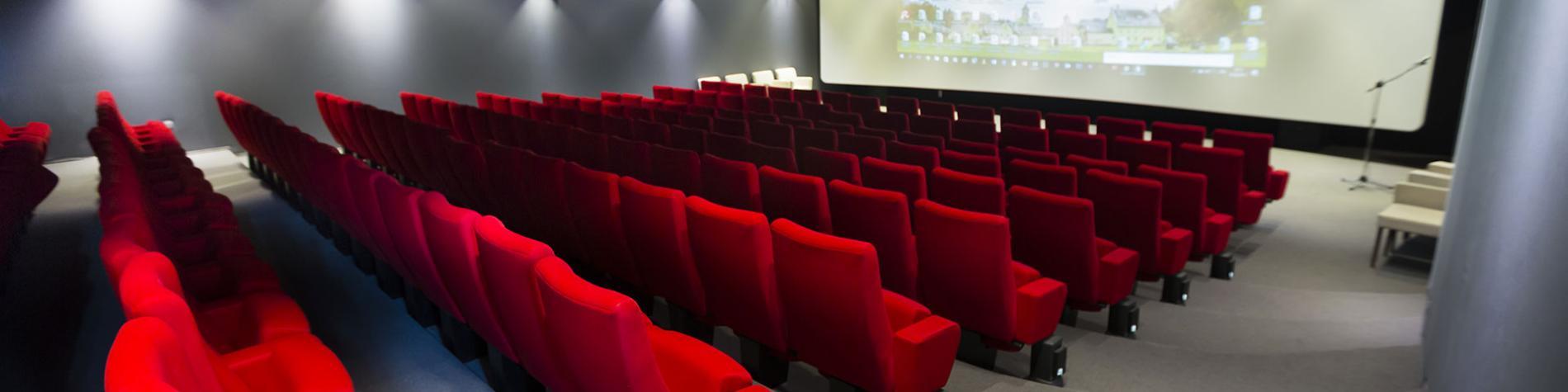 salle avec siège rouge et grand écran