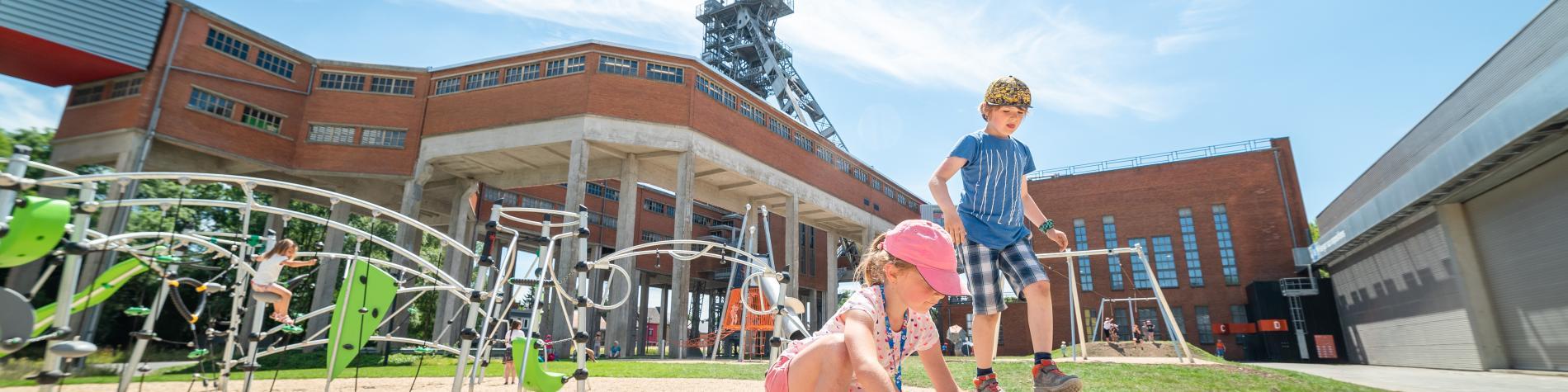 Deux enfants profitent de la plaine de jeux du Pass, musée des sciences, à Frameries