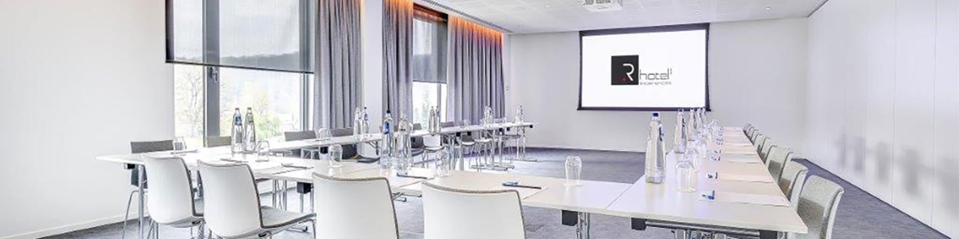 salle de séminaire en U avec chaises blanches et rétro-projecteur ainsi que lumière du jour. Parfait pour vos événements d'affaires en Wallonie