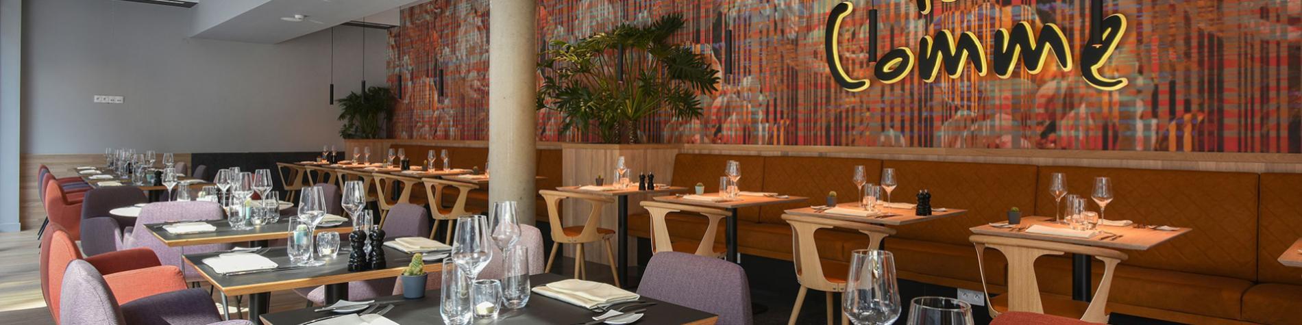 salle de restaurant avec tables dressées et inscription sur le mur