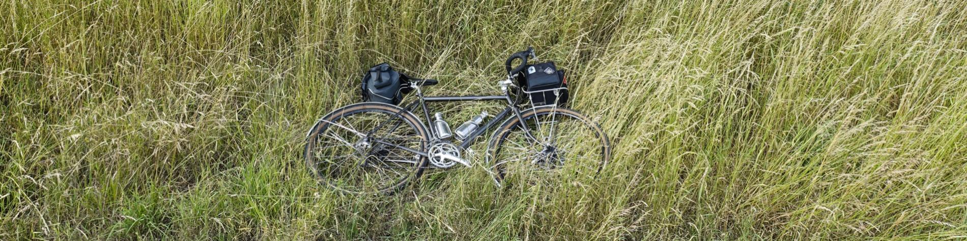 Vélo posé dans l'herbe en campagne