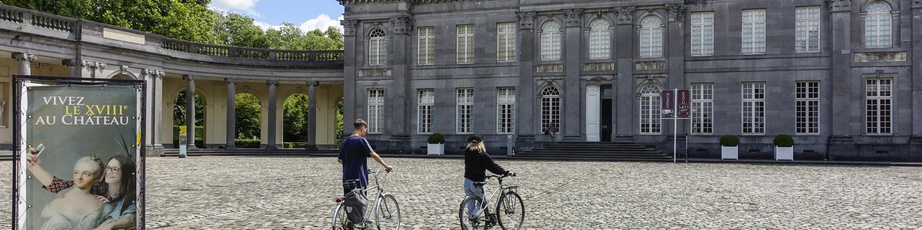 2 personnes à vélo devant le Château de Seneffe
