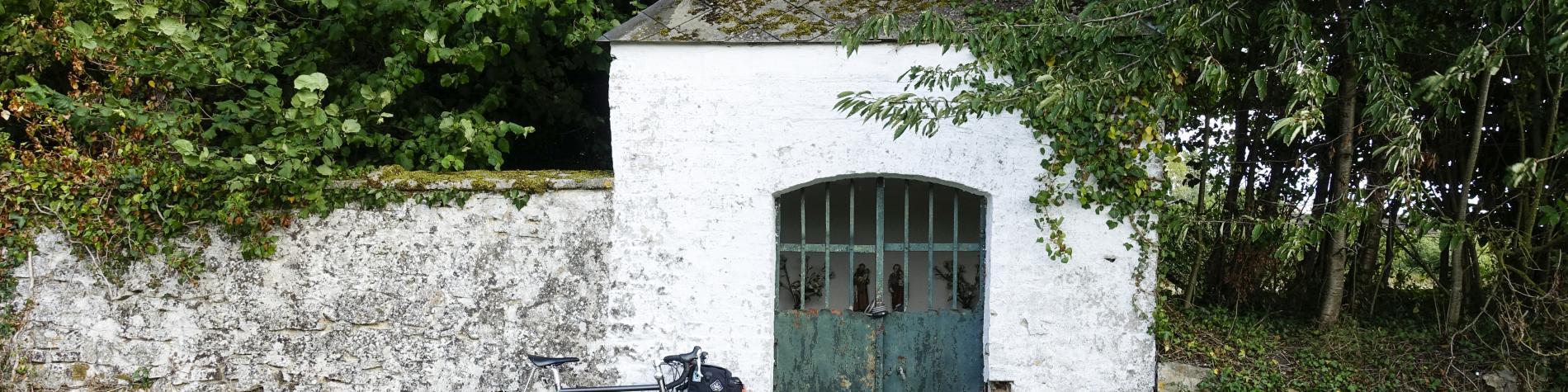 Vélo posé contre une maisonnette blanche