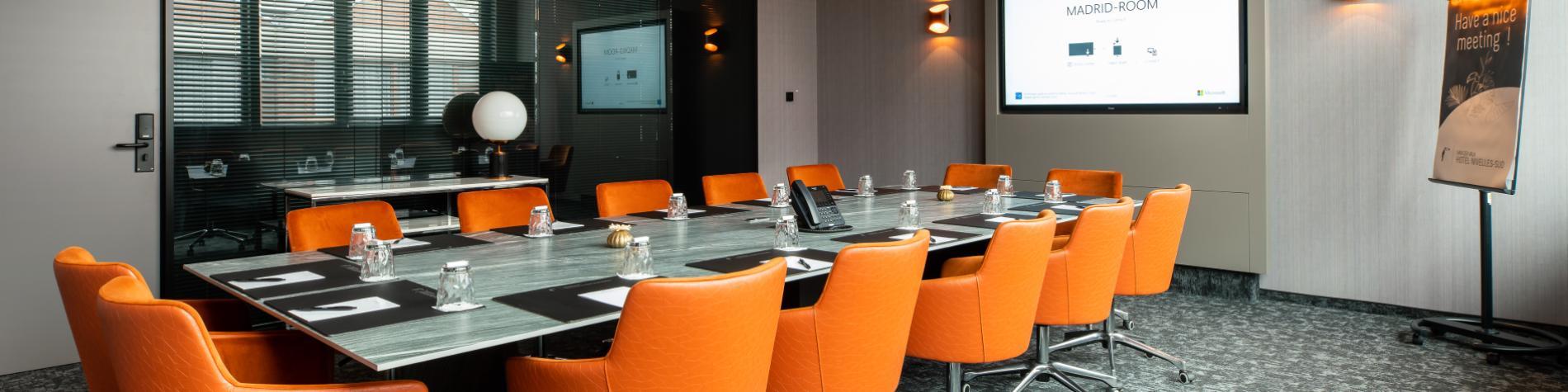 Salle de réunion avec chaises orange du Van der Valk Nivelles-Sud