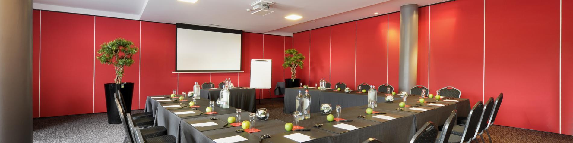 salle de réunion en Wallonie avec mur rouge et tables en U
