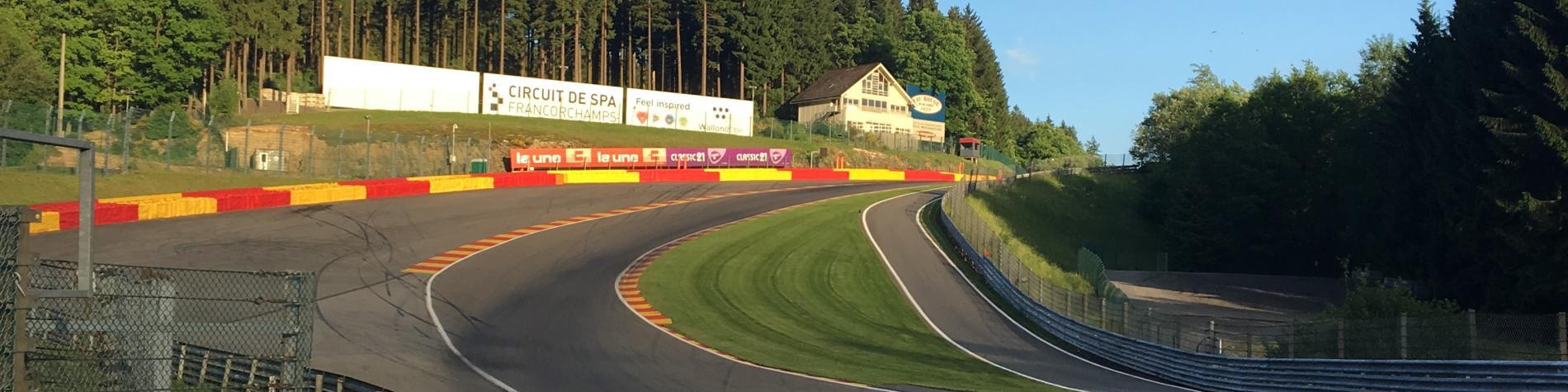 circuit de course en chicane avec ciel bleu et espace boisé en Wallonie