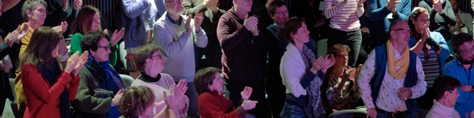 Ensemble de personnes applaudissant dans une salle