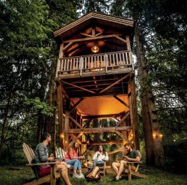 Vue extérieure d'une soirée entre amis au pied d'une des cabanes perchées de Rensiwez